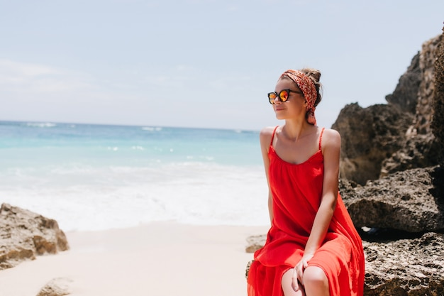 Fascinating white female model enjoying ocean views through sunglasses. outdoor photo of relaxed young lady in red dress posing on rock near sea.