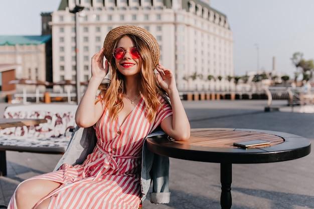 屋外カフェに座っている麦わら帽子の魅力的な白人の女の子。街で身も凍るような美しい縞模様のドレスを着た陽気なヨーロッパの女性の肖像画。