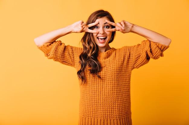 재미있는 얼굴을 만들고 웃 고 매혹적인 백인 여자. 화려한 소녀의 스튜디오 초상화는 니트 오렌지 복장을 착용합니다.