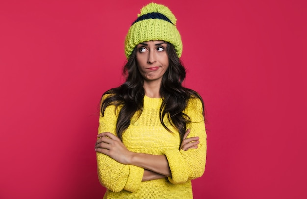 Fascinating woman in a bright yellow sweater and a green hat with pompom is posing in front with her arms folded, looking to the left with a skeptical facial expression