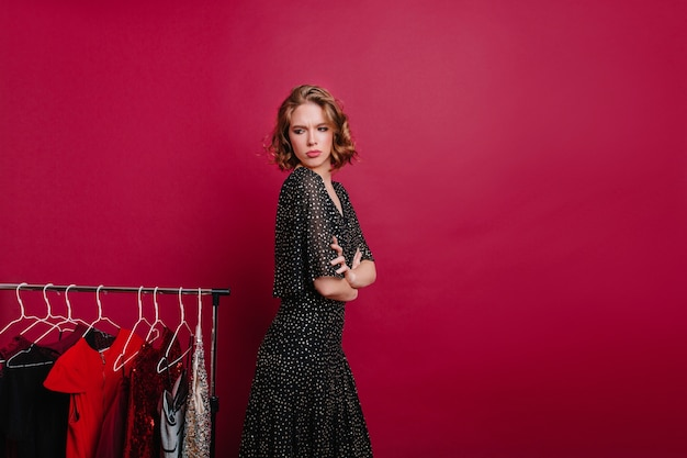Fascinating woman expressing sad emotions in boutique with expensive clothes