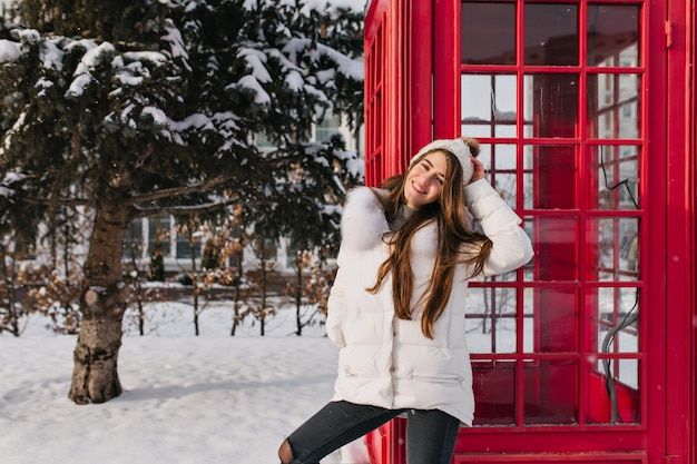 Fascinating woman with long hair standing near red phone booth and smiling