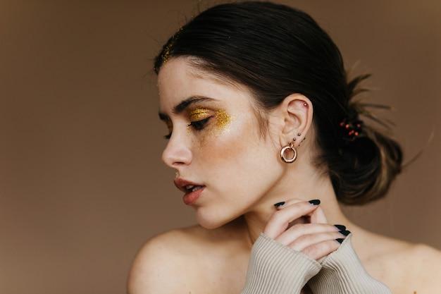 パーティーメイクポーズの魅力的な女性。リラックスしたブルネットの女の子の屋内クローズアップ写真はイヤリングを着用しています。