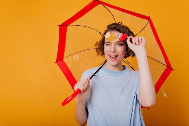 Affascinante giovane signora con gli occhiali che si diverte durante il servizio fotografico con l'ombrello. studio shot di adorabile ragazza riccia scherzare mentre posa con l'ombrellone.