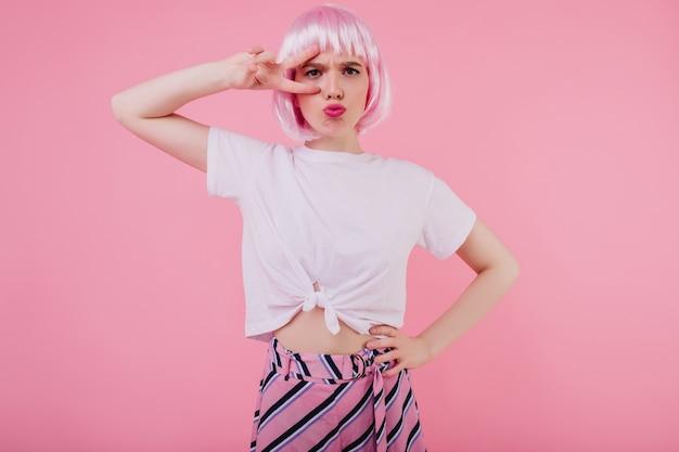 Очаровательная барышня с ярким макияжем корчит рожи во время. крытый портрет красивой девушки в блестящем парике, изолированной на розовой стене