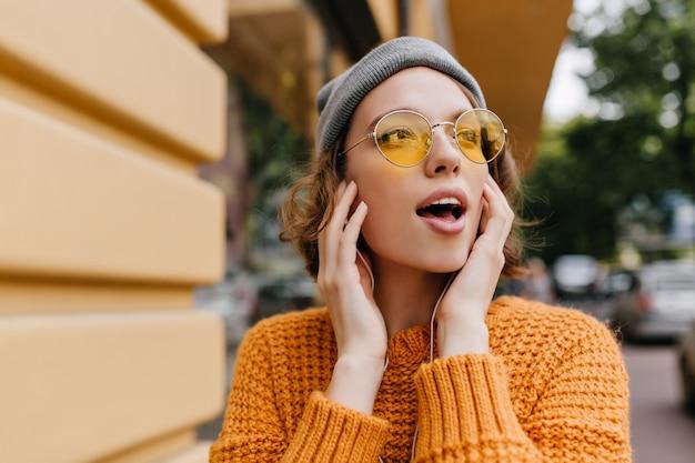 Affascinante giovane donna in occhiali da sole vintage guardandosi intorno trascorrere del tempo all'aperto