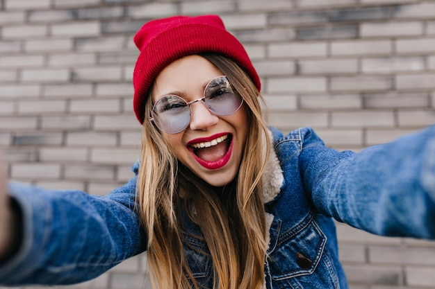 벽돌 벽에 셀카를 만드는 밝은 화장으로 매혹적인 젊은 여자. 파란 안경에 꿈꾸는 백인 여성 모델과 자신의 사진을 찍는 데님 재킷의 사진.