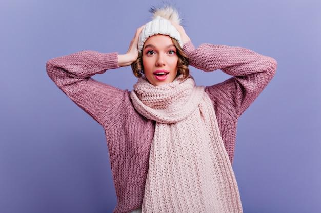 Очаровательная молодая женщина с каштановыми волосами нежно улыбается и трогает голову. крытый портрет беззаботной европейской леди с розовым макияжем в зимней шапке.