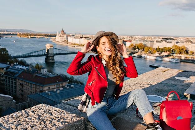 Affascinante giovane donna con capelli castani tenendo il cappello e ridendo sullo sfondo della città
