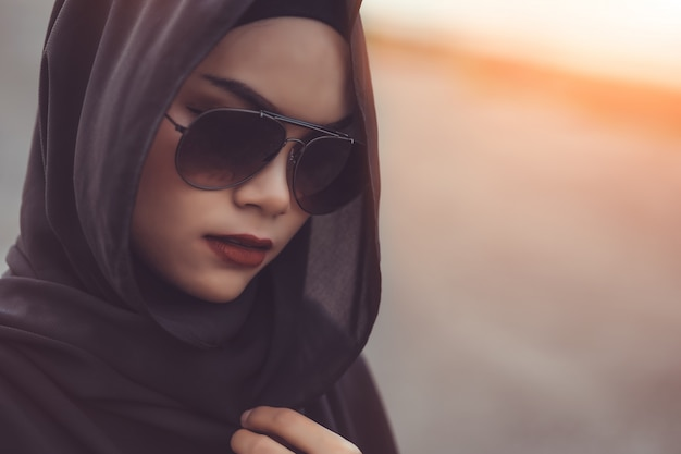 Fashi portrait of young beautiful muslim woman with the black hijab and sunglasses.vintage style