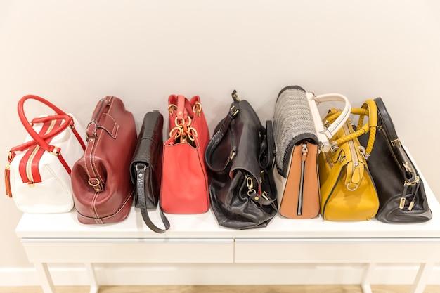 Коллекция fashinable сумок, стоящих на полке в ряд
