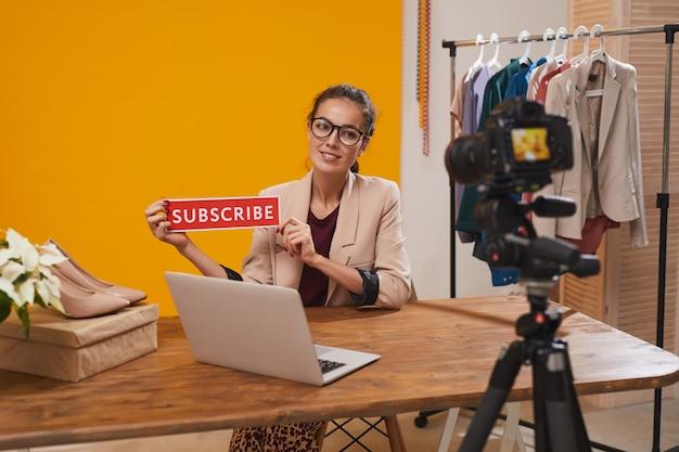Fashio blogger holding subscribe button