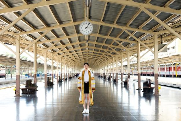 ファッション20代アジアの女性はゴールドラインのクリーム色の豪華なコートドレスを着ています。若い女の子は笑顔で夏の駅の鉄道で電車で旅行します