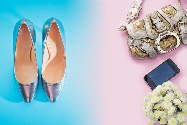 Fashion accessories shoes handbag shoes silver gradient blue bouquet flowers pink background.