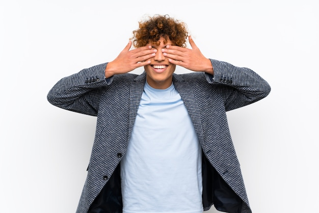 Fashion african american man over isolated white wall covering eyes by hands
