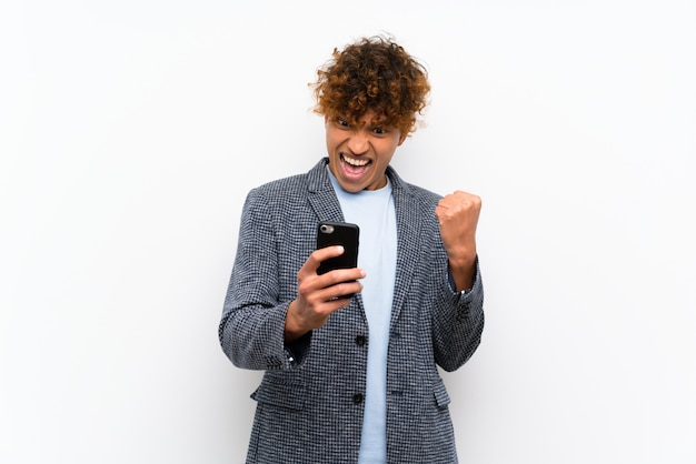 Fashion african american man over isolated white wall with phone in victory position