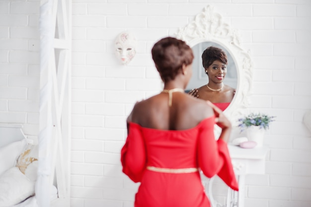Fashion african american model in red beauty dress, sexy woman posing evening gown and looking at mirror.