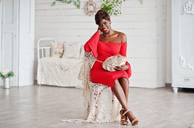 Fashion african american model in red beauty dress, sexy woman posing evening gown sitting at chair in white vintage room.