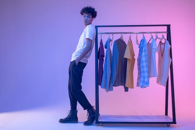 패션. 옷을 옷걸이 근처에 서 아프리카 계 미국인 젊은 남자
