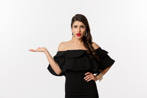 패션과 뷰티. 검은 드레스를 입은 성가신 여성이 손을 들고 카메라를 보고 혼란스러워하며 흰색 배경 위에 서 있는 것이 어떤 제스처입니다.