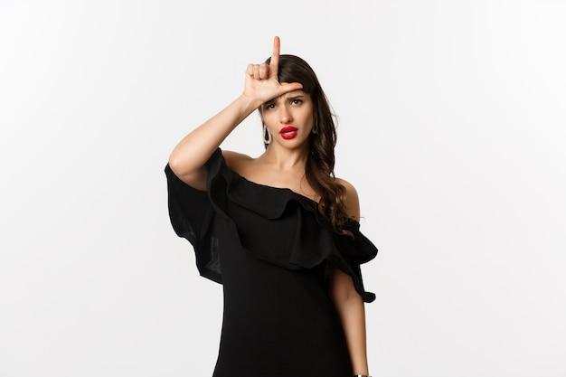 Мода и красота. высокомерная гламурная женщина показывает знак проигравшего на лбу, насмехаясь над потерянным человеком, стоящим в черном платье на белом фоне.
