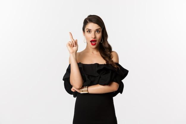 Мода и красота. привлекательная кавказская женщина в черном платье, имея идею, поднимая палец и говоря предложение, белый фон.