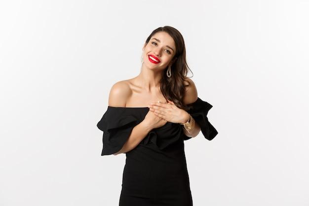 Мода и красота. привлекательная женщина очарования в черном платье, говоря спасибо, улыбаясь и держась за руки на сердце с довольными эмоциями, на белом фоне.