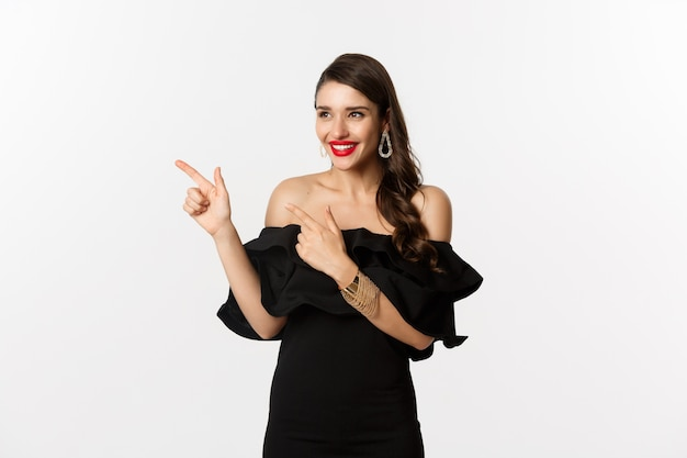 패션과 뷰티. 보석, 메이크업 및 검은 드레스에 매력적인 여자, 웃음과 프로 모션 제공, 흰색 배경에서 왼쪽 손가락을 가리키는.