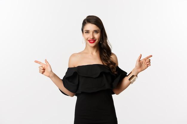 패션과 뷰티. 보석, 메이크업 및 검은 드레스에 매력적인 여자, 웃으면 서 손가락 옆으로 복사 공간 제공, 흰색 배경을 가리키는.
