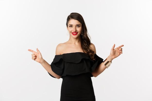 패션과 뷰티. 보석, 화장, 검은 드레스를 입은 매력적인 여성, 웃고 손가락을 옆으로 가리키는 카피 공간 제공, 흰색 배경