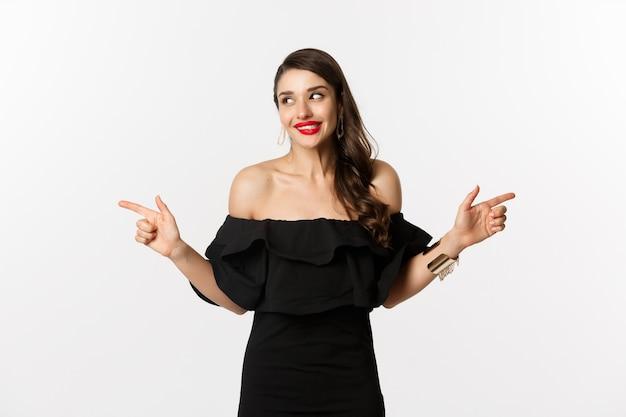 패션과 뷰티. 보석, 메이크업 및 검은 드레스에 매력적인 여자 웃 고 손가락 옆으로 복사 공간 제공, 흰색 배경을 가리키는.