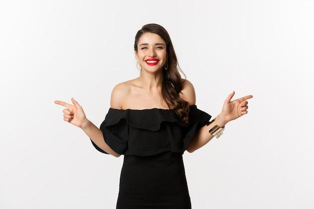 패션과 뷰티. 보석, 메이크업, 검은 드레스를 입은 매력적인 여성, 웃고 손가락을 옆으로 가리키며 공간 제안, 흰색 배경을 복사합니다.