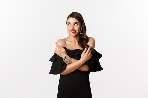 패션과 뷰티. 검은 드레스에 아름 다운 매력적인 여자, 선택, 유혹에서 입술을 물고 옆으로 가리키는, 흰색 배경 위에 서있는.
