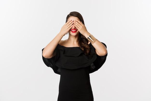 Мода и красота. красивая женщина в черном платье и красной помаде, прикрывая глаза и улыбаясь, ожидая сюрприза, стоя на белом фоне.