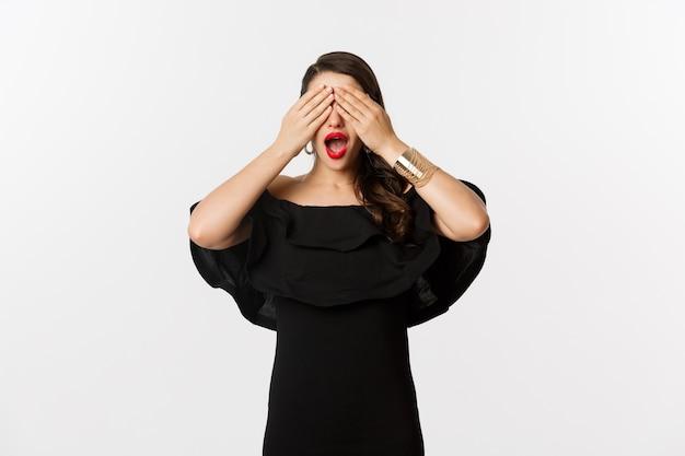 ファッションと美容。黒のドレスと赤い口紅の美しい女性、目を覆って笑顔、驚きを待って、白い背景の上に立っています。