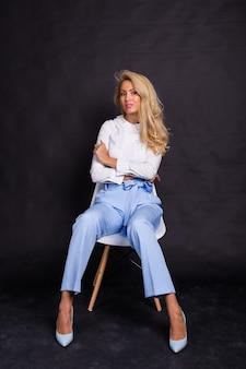 패션과 뷰티 개념-흰 셔츠와 청바지에 아름다운 금발 모델은 의자에 앉아