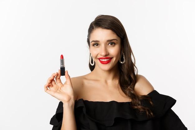 ファッションと美容のコンセプト。赤い口紅と化粧を適用し、パーティーに行く、白い背景の上に立っている黒いドレスの美しい女性。