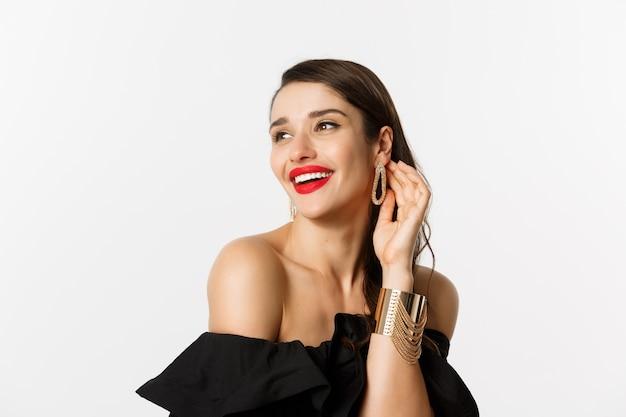 패션과 뷰티 개념. 붉은 입술, 검은 드레스, 요염한 웃음과 멀리 응시, 흰색 배경 위에 서있는 우아한 갈색 머리 여자의 클로즈업.