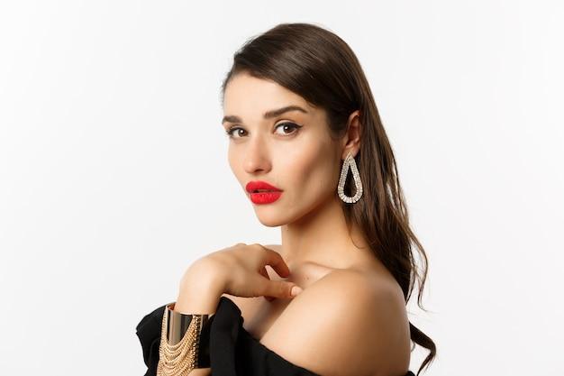 ファッションと美容のコンセプト。赤い唇、化粧、イヤリング、自信を持ってカメラを見て、白い背景の上に立っているエレガントな女性のクローズアップ。