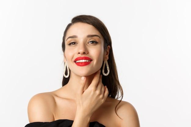 ファッションと美容のコンセプト。赤い唇、顔に触れ、自信を持って笑顔、白い背景の上に立っているゴージャスなブルネットの女性のクローズアップ。