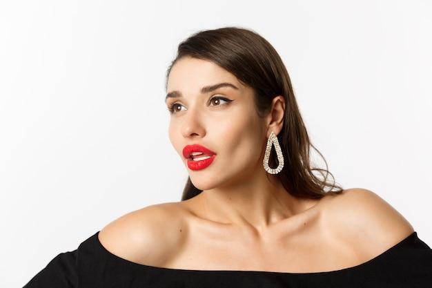 ファッションと美容のコンセプト。赤い唇、イヤリング、黒いドレス、官能的な目をそらし、白い背景の上に立っている豪華な女性のクローズアップ。