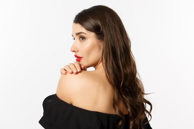 패션과 뷰티 개념. 우아한 여자는 어깨에 기대어 관능적 인 피어싱 눈으로 옆으로 응시하고 메이크업과 빨간 립스틱을 입고 흰색 배경 위에 서 있습니다.