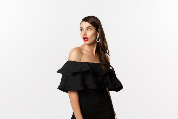 Концепция моды и красоты. изображение молодой женщины в черном платье поворачивает позади и смотрит на космос экземпляра, стоя над белой предпосылкой.