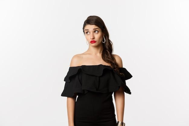 Мода и красота. путать привлекательная женщина в черном платье, глядя в сторону с озадаченным и шокированным лицом, стоя на белом фоне.
