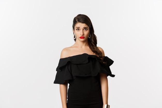 ファッションと美容。カメラで混乱して悲しそうに見える黒いドレスを着たキュートで臆病な若い女性は、理解できず、白い背景に対して暗い立っています。