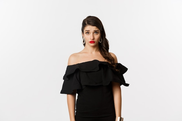 Мода и красота. милая и робкая молодая женщина в черном платье, смущенная и грустная в камеру, не может понять, мрачно стоит на белом фоне.