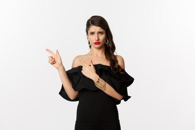 패션과 뷰티. 실망한 매력적인 여자가 불평하고, 검은 드레스를 입고, 찡그리고 손가락이 나쁜 제안, 흰색 배경에 남아 있습니다.