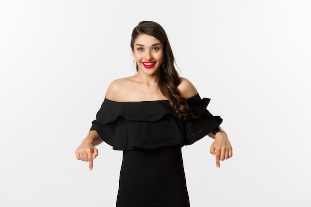 Мода и красота. элегантная женщина в черном платье указывая пальцами вниз, показывая промо и улыбаясь, стоя на белом фоне.