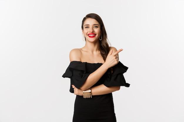 ファッションと美容。赤い唇、黒いドレス、笑顔とロゴに指を指して、白い背景の上に立っているエレガントな女性。