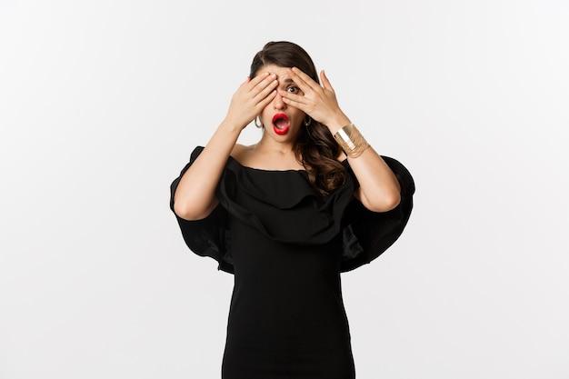 패션과 뷰티. 눈을 덮고 있지만 손가락을 통해 엿보기 검은 드레스에 충격 된 매력적인 여자의 이미지는 흰색 배경 위에 서 깜짝 놀랐습니다.